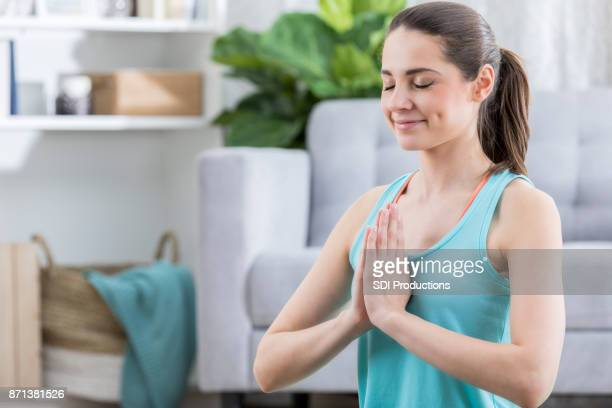 Young woman performs namaste yoga pose at home