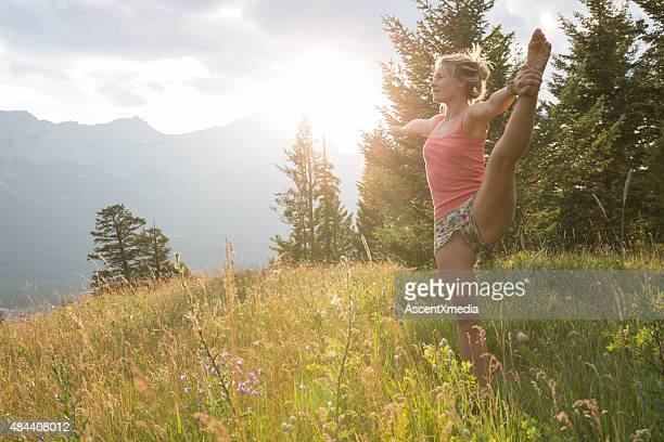 Young woman performs stretching exercises in mountains