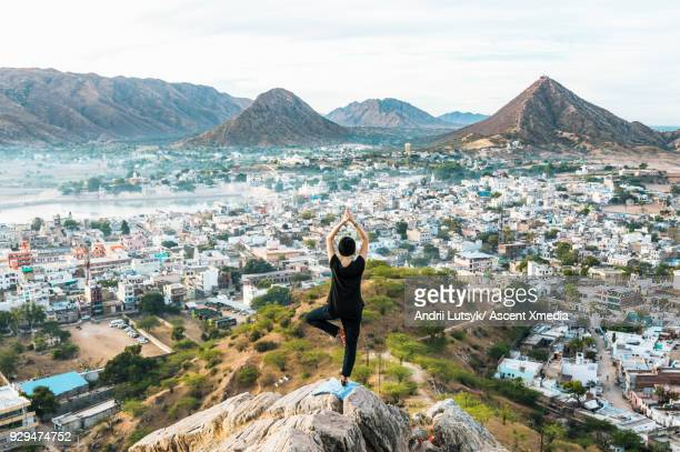 Young woman performs yoga move above city and mountains in shawl