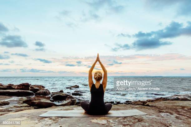 young woman performs yoga moves on bluff above sea - 無の境地 ストックフォトと画像
