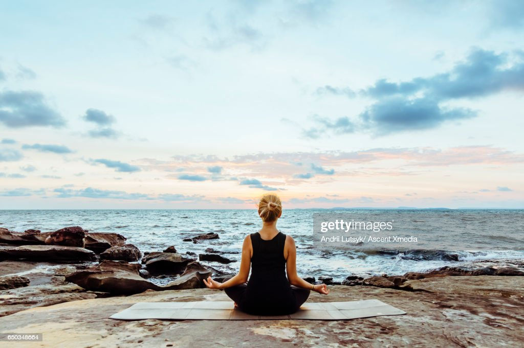 Young woman performs yoga moves on bluff above sea : Stock Photo