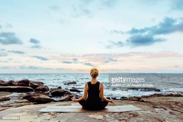 young woman performs yoga moves on bluff above sea - mindfulness stock pictures, royalty-free photos & images