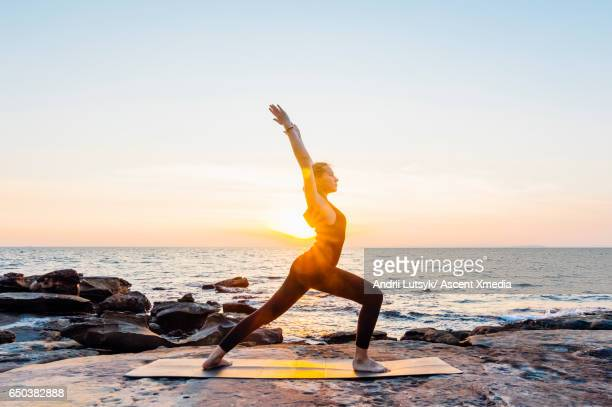Young woman performs yoga moves on bluff above sea