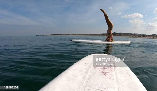 junge frau führt yoga-moves auf paddelbrett - 20 24 jahre stock-fotos und bilder