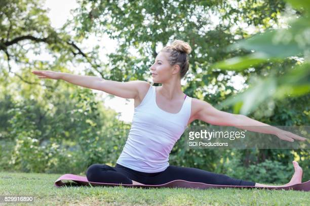 jeune femme effectue l'yoga en plein air avec les bras tendus - gymnastique au sol photos et images de collection