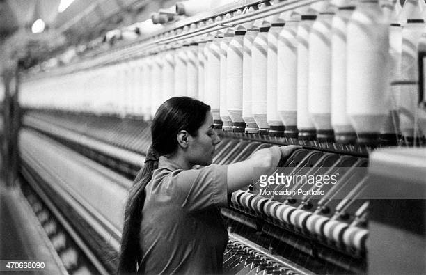 A young woman personally checks the proper functioning of a large industrial loom supplied by big spools of thread the woman with a ponytail...