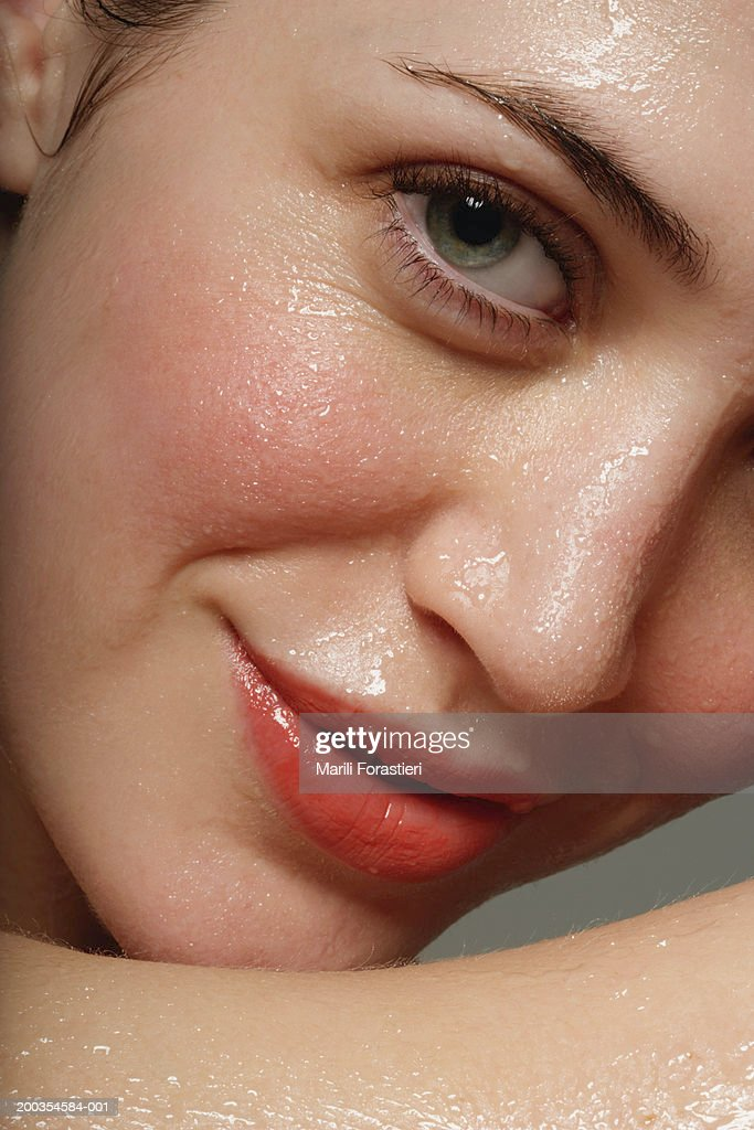 Young woman perspiring, smiling, portrait, close-up : Stock Photo