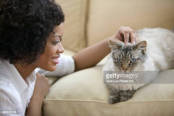 Young woman petting a cat