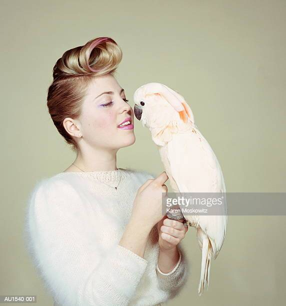 young woman petting cockatoo, portrait (brightly lit) - pompadour stock pictures, royalty-free photos & images