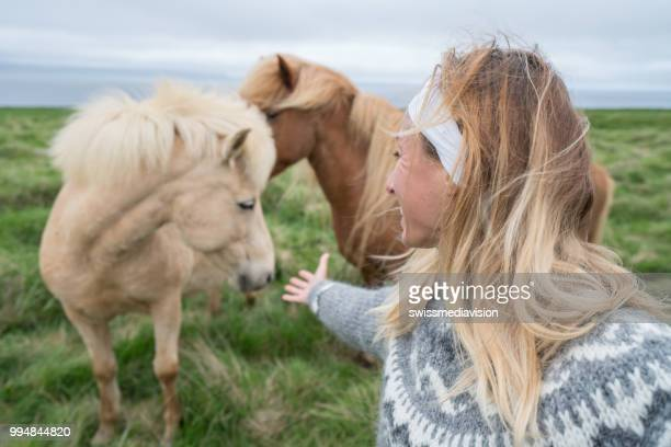 Young woman petting Icelandic horse in meadow