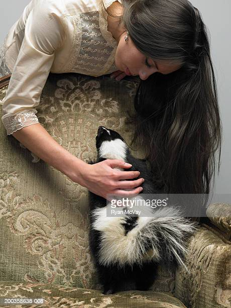 Young woman petting skunk on armchair