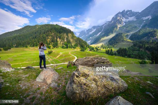 young woman photographer taking photo of thajiwas park in kashmir, india - kashmir valley stock pictures, royalty-free photos & images