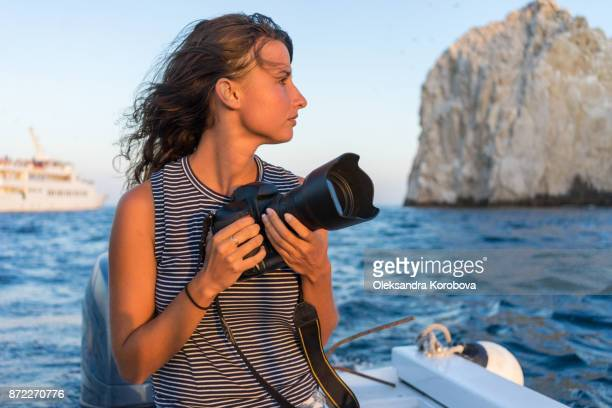 young woman photographer with her camera on the boat at sunset. - hot women on boats stock pictures, royalty-free photos & images