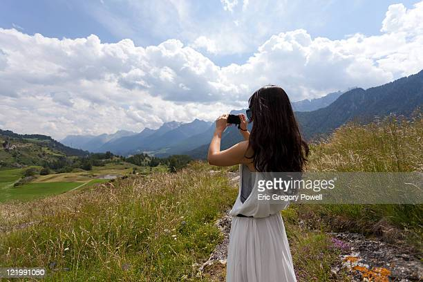A young woman photographing a Swiss valley