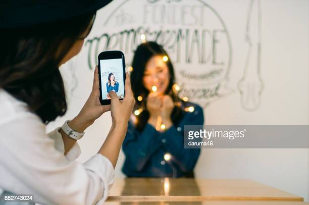 young woman photographing a young woman holding illuminated led lights in bright room - influencer stock photos and pictures