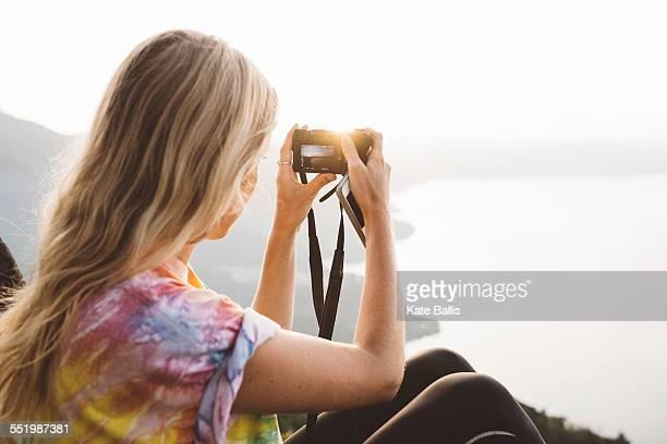 Young woman photographing at Lake Atitlan on digital camera, Guatemala