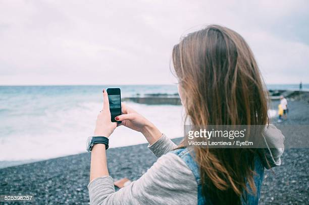 Young Woman Photographing At Pebble Beach