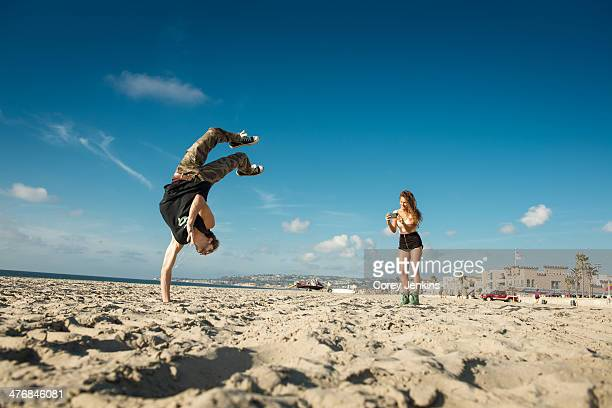 Young woman photographing boyfriend doing backflip on San Diego beach