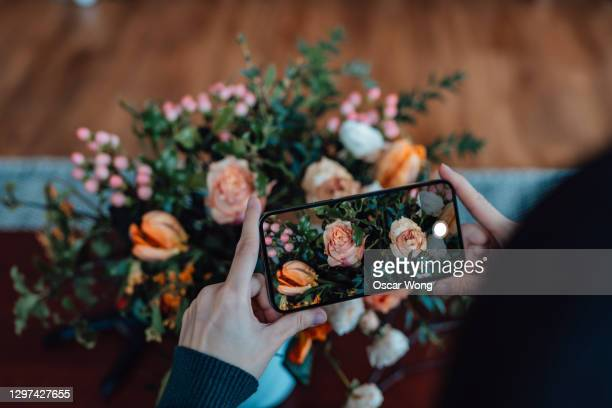 young woman photographing bunch of flowers with smartphone - mobile phone stock pictures, royalty-free photos & images