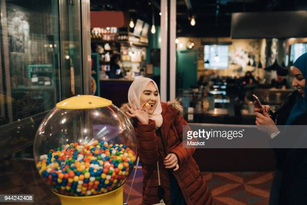 young woman photographing cheerful female friend standing with bubble gum by vending machine - gumball machine stock pictures, royalty-free photos & images