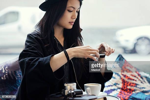 Young woman photographing coffee through smart phone in creative office