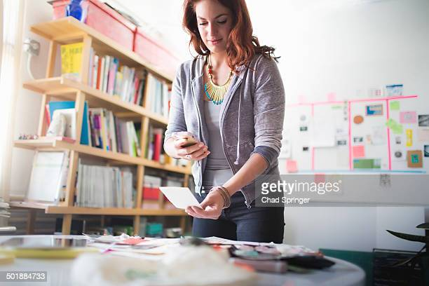 young woman photographing documents with smartphone - fotohandy stock-fotos und bilder