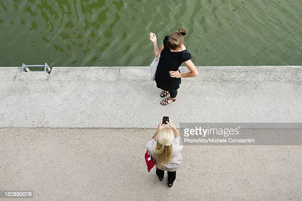 Young woman photographing friend with cell phone, elevated view