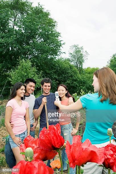 Junge Frau Fotografieren Freunden in der community garden