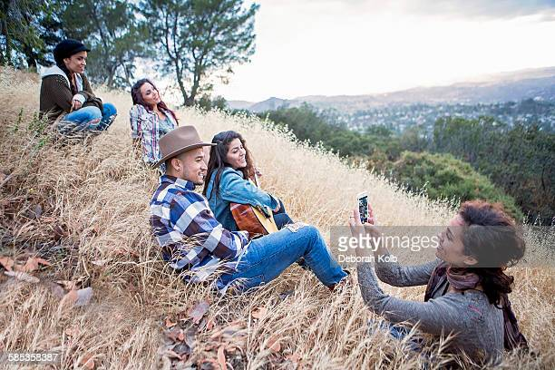 Young woman photographing her four adult siblings on grassy hill