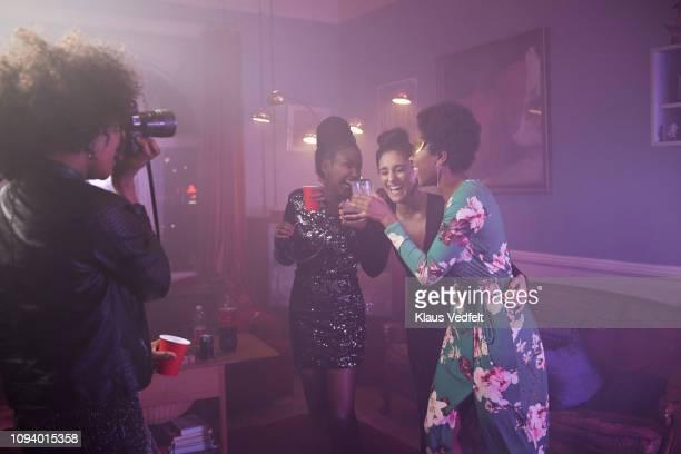 young woman photographing her friends dancing - grupo pequeno de pessoas - fotografias e filmes do acervo
