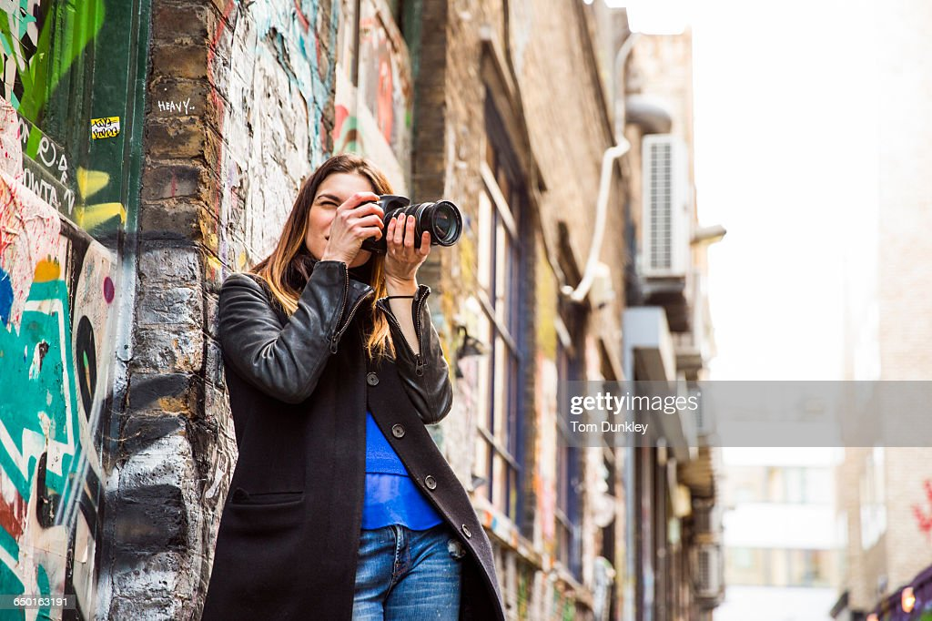 Young woman photographing in graffiti alley using DSLR : Stock Photo