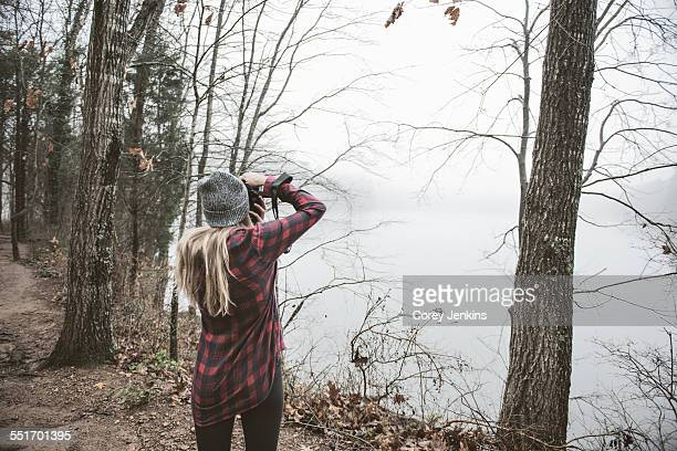young woman photographing misty lake - cary stockfoto's en -beelden