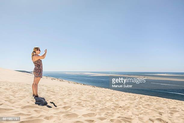 Young woman photographing sea with smartphone, Dune de Pilat, France