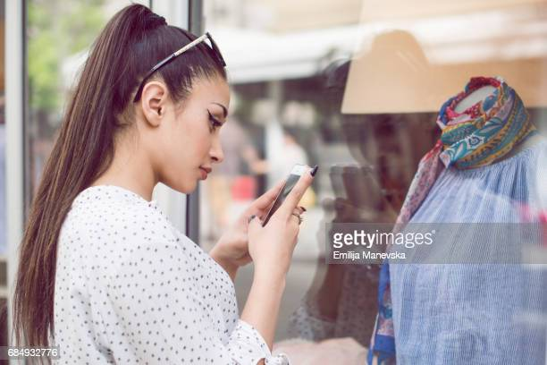 Young woman photographing shop window with camera phone