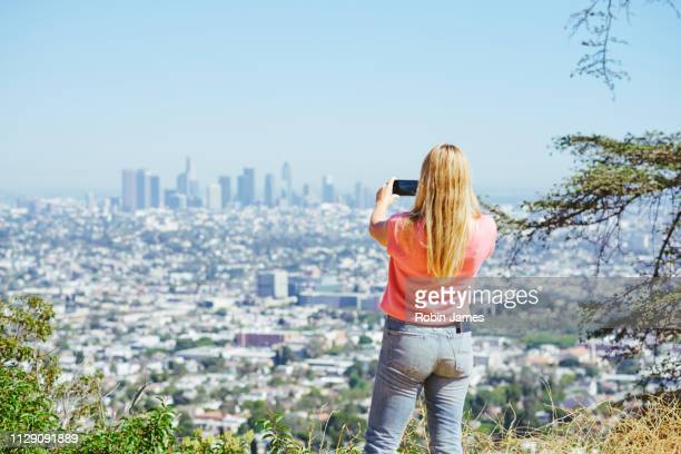 young woman photographing skyline from hilltop, rear view, los angeles, california, usa - 丘 ストックフォトと画像