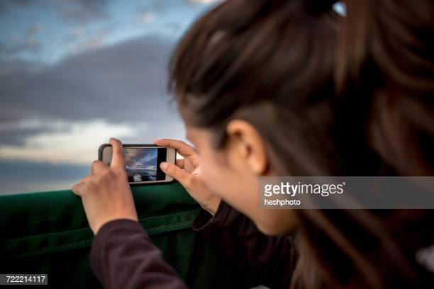 young woman photographing sunset from boat on coast of maine, usa - heshphoto stock pictures, royalty-free photos & images