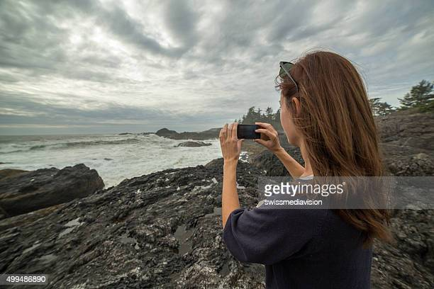 Young woman photographing the cliffs landscape with her mobile phone