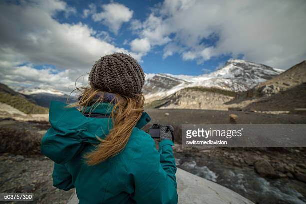 Young woman photographing the landscape with her digital camera