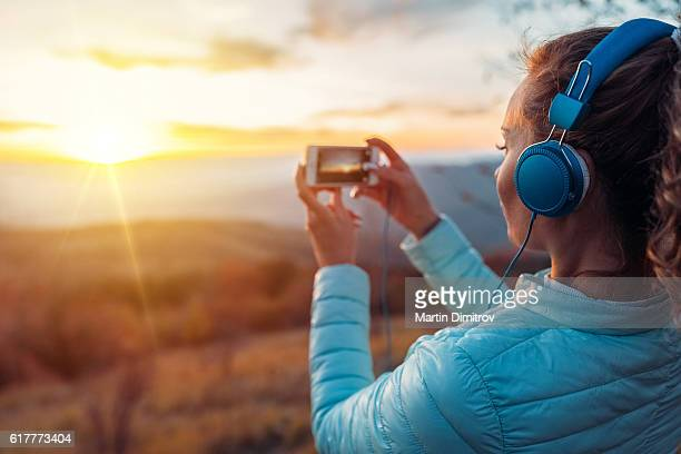 Young woman photographing the sunset