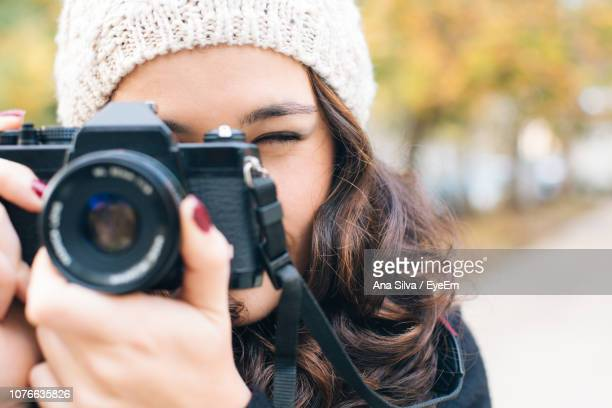 Young Woman Photographing Through Camera In City During Winter