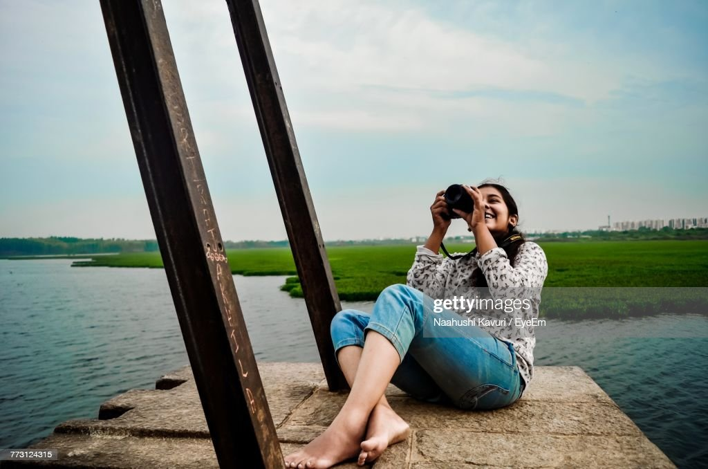 Young Woman Photographing Through Camera While Sitting Against Lake : Photo