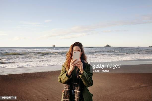 young woman photographing through smart phone on beach - obscured face stock pictures, royalty-free photos & images