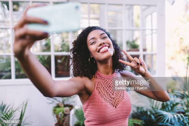 Young Woman Photographing Through Smart Phone Outdoors