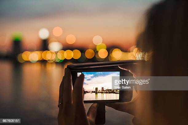 Young woman photographing view with smartphone, close-up of screen