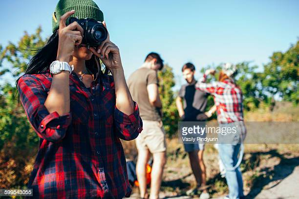 Young woman photographing while friends standing in background