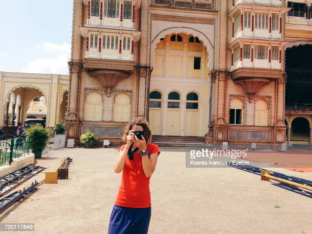 Young Woman Photographing While Standing Against Historic Building