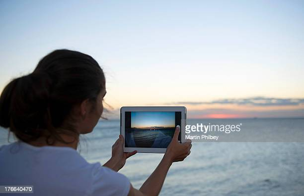 Young woman photographing with her digital tablet at sunset