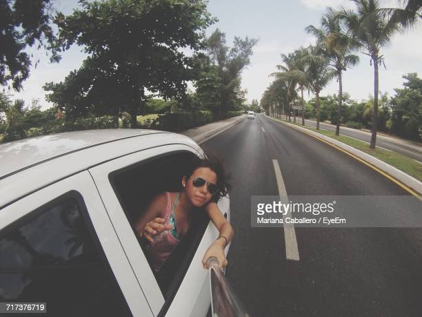 Young Woman Photographing With Selfie Stick While Sitting In Car