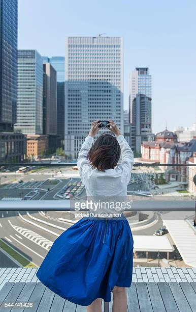 young woman photographing with smartphone in city. - skirt blowing stock photos and pictures