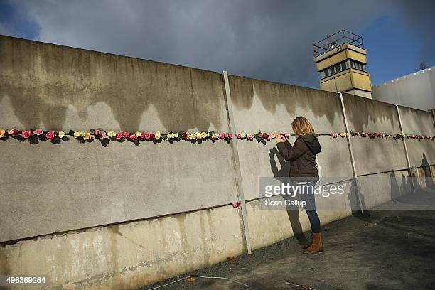 A young woman photographs flowers left by other visitors at the Berlin Wall memorial at Bernauer Strasse on the 26th anniversary of the fall of the...